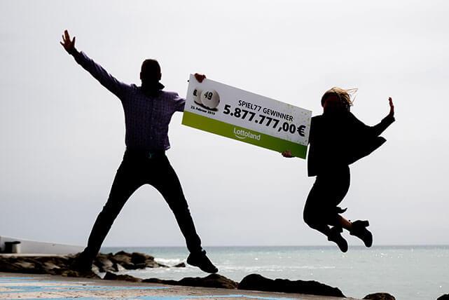 Ny lotto vinnare gör ett glädjehopp med check